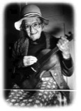 Sylvia Curley holding her father's fiddle
