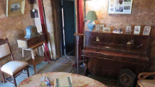 Sitting room at Mugga-Mugga showing a table, chairs and a small upright piano