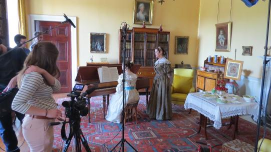 Filming in the Yellow Drawing Room at Tatton Park, showing a piano lesson in progress and the film crew